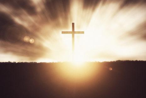 Christian cross at sunset on grass field background.